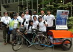 "Seattle Books on Bikes librarians pose with their book trailer and the sign that reads ""Your Library Without Limits!"""