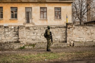 A Russian soldier at the Ukrainian Military Artillery Base in Simferopol, Crimea. Image via Shutterstock.