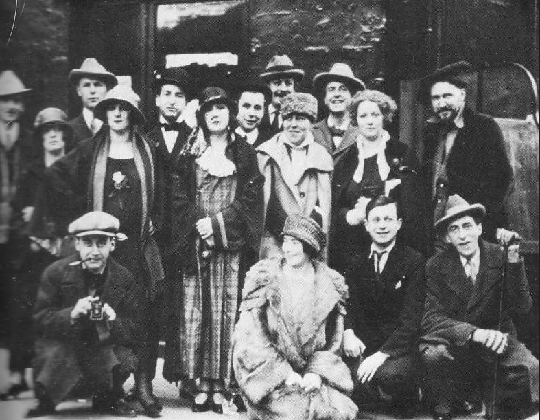 The Crowd outside The Jockey in Paris in 1923. Front row: Man Ray, Mina Loy, Tristan Tzara, Jean Cocteau Middle row: Kiki, Margaret Anderson, Jane Heap, unidentified, Ezra Pound Top row: Bill Bird on the left, Hilaire Hiler and Curtiss Moffit on the right